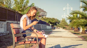 Young girl with skateboard and headphones looking smartphone Royalty Free Stock Image