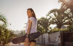 Young girl with a skateboard outdoor Royalty Free Stock Photos
