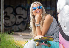 Young girl with skateboard sitting outdoors Stock Photos