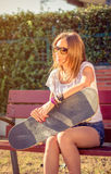 Young girl with skateboard sitting outdoors on Royalty Free Stock Photo