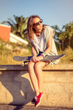 Young girl with skateboard sitting over the wall Royalty Free Stock Image