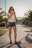 Young girl with a skateboard using the smartphone outdoor Royalty Free Stock Image
