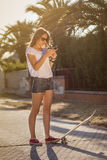 Young girl with a skateboard using the smartphone outdoor Stock Images