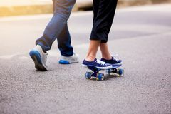 Young girl skateboarding with her dad running at park outdoor i stock photos