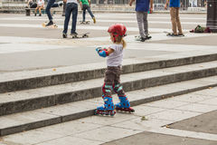 Young girl skater in  foreground adjusts her protective gloves w Stock Photos