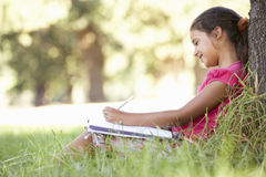 Young Girl Sketching In Countryside Leaning Against Tree Stock Photo