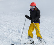Young girl (9-11) skiing in bright yellow pants with orange helm Royalty Free Stock Photo