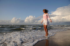 Young girl skipping on the beach stock photo