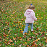 Young girl skipping in the fall leaves. Cute young girl skipping in the autumn leaves of a playgrond Royalty Free Stock Photography
