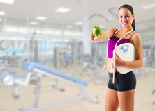 Young girl with skipping rope and apple at gym club Royalty Free Stock Photography