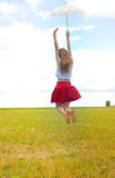 Young girl in skirt with lace umbrella jumping on. Picture of amazed young girl in red skirt with white lace umbrella. Excited woman jumping on summer Stock Image