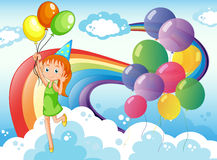 A young girl at the sky with balloons and rainbow Stock Photo