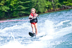 Young Girl on Slalom Ski. A young girl (7 years old) slalom skiing behind a boat Stock Image