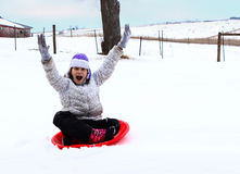 Young Girl Sledding. A young girl having fun sledding on a cold winter day royalty free stock photography