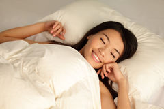 Young girl sleep peaceful  at night. Young girl sleep peaceful with smile on home bed at night , model is a asian woman Royalty Free Stock Image