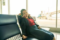 Young girl sleeping in airport. Young Asian girl sleeping in the airport royalty free stock photos