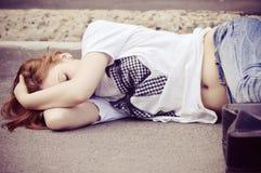 Young girl sleeping on asphalt Stock Image