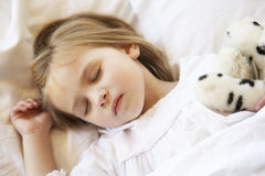 Young Girl Sleeping In Bed With Soft Toy Stock Photo