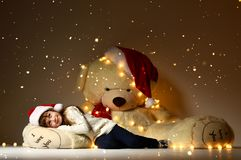 Young  girl sleeping with big soft teddy bear toy in christmas santa red hat looking up on shining light. S on dark background Royalty Free Stock Photo