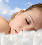 Young girl sleeping with clouds. Portrait of a young girl sleeping with clouds royalty free stock image