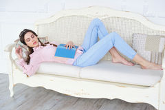 Young girl sleeping on a couch with her book Stock Photography