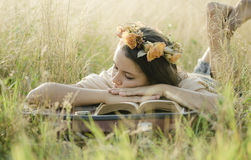 A young girl sleeping with her head on a book. She`s anjoying to sleep in nature stock photo
