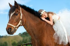Young girl sleeping on horseback. Royalty Free Stock Image