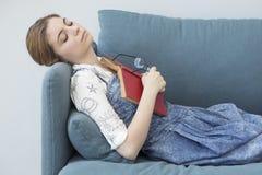 Young girl sleeping while reading book Royalty Free Stock Photos
