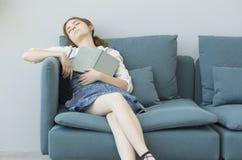 Young girl sleeping while reading book Stock Photos