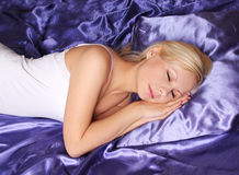 Young girl sleeping on silk  bed Stock Images