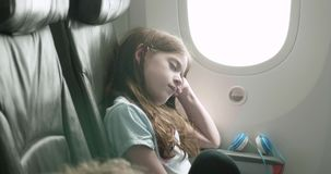 Young girl sleeps with her head resting against the bulkhead on a plane. As the camera pans around her stock footage