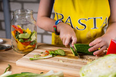 Young girl slicing dill cucumber for bottling Royalty Free Stock Photography