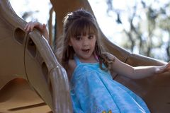 Young girl on slide at playground. Young girl on slide at park playground Royalty Free Stock Photo