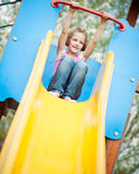Young girl on slide in playground Stock Image