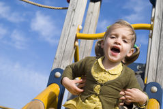 Young girl on slide in playground Royalty Free Stock Images