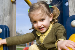 Young girl on slide in playground Stock Photos