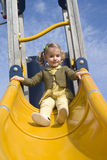 Young girl on slide in playground Royalty Free Stock Photos