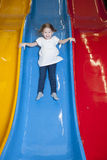 Young girl slides down colorful slide Stock Images