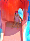 Young girl sliding down a water slide in summer Stock Photos