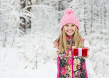 Young girl with small red gift box showing thumbs up in winter forest Royalty Free Stock Image