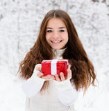 Young girl with small red gift box standing in winter forest Stock Photo