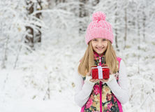 Young girl with small red gift box in winter forest Stock Photo