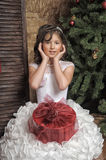 Young girl in a smart white dress with a gift in Christmas Royalty Free Stock Photo
