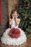 Young girl in a smart white dress with a gift in Christmas Royalty Free Stock Image