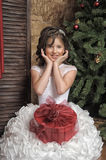 Young girl in a smart white dress with a gift in Christmas Stock Photography