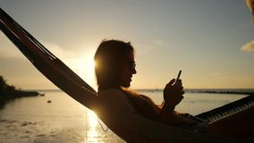 Young Girl with Smartphone in Hammock Silhuette Against Beautiful Sunset at the Beach. Koh Phangan, Thailand. HD stock footage