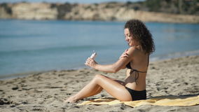 Young girl smears sunscreen on hands on the beach. Young curly brunette sits on the cover on the beach. Pretty girl smears sunscreen on her hands. Cute young stock video footage