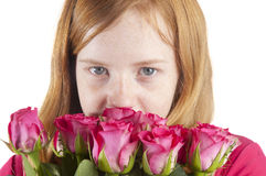 Young girl is smelling at beautiful pink roses Stock Image
