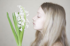 Young girl smelling the flower. A young girl smelling the flower hyacinthus Stock Images