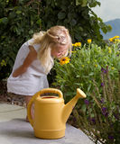 Young girl smelling flowers Stock Image
